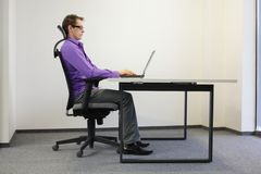 Correct sitting position at laptop Stock Images