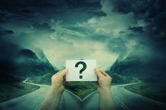 The correct way. Hands holding a sheet with question mark, in front of a crossroad, fork junction where a road is splitted in two different ways. Lost people royalty free stock photos
