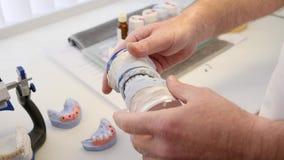 Correcte beet van tanden, kunstmatige kaken in handen van de mens tegen witte lijstachtergrond stock video