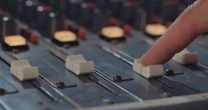 Correcte ingenieur die een het mengen zich console in een opnamestudio aanpassen stock footage