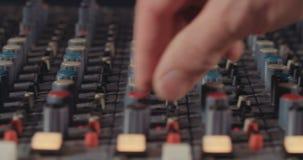 Correcte ingenieur die een het mengen zich console in een opnamestudio aanpassen stock video