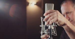 Correcte ingenieur die een microfoon in een opnamestudio aansluiten stock footage