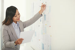 Correcting blueprint. Project manager correcting blueprint according to document Stock Photo