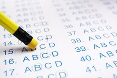 Correcting mistake with pencil eraser in answer sheet. Closeup stock photography