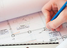 Correcting the plans. Close-up shot of architecture plans and hand holding lead-holder Stock Photos