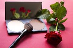 Correcting powder, brush, red rose on pink surface. Royalty Free Stock Image