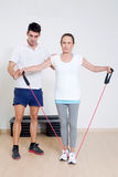 Correcting a skipping rope exercise. Personal coach correcting a stretching exercise Stock Image