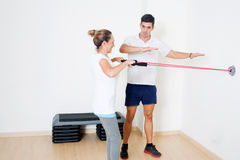 Correcting a skipping rope exercise. Personal coach correcting a stretching exercise Stock Photos