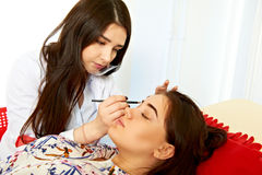 Correction of eyebrows in a beauty salon Stock Photo