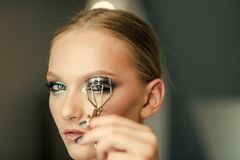 Correction of eyelashes. Portrait of young beautiful woman making curl eyelashes using curling cosmetic tool.  royalty free stock photography