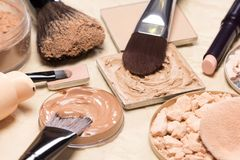 Corrective makeup products and accessories close-up. Foundation, powder, concealer with make-up brushes on crumpled paper. Corrective makeup products and Stock Photography