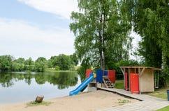 A corrediça em mudança da cabine e de água na praia suporta Fotografia de Stock