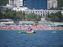 Corrediça inflável alta no mar contra o contexto da costa com praias, hotéis e as árvores verdes imagem de stock