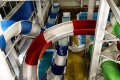 Corrediças coloridas no parque interno da água imagem de stock royalty free