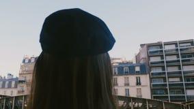 Corrediças da câmera atrás do turista fêmea feliz que toma a foto do smartphone da opinião da torre Eiffel de Paris do balcão do  filme
