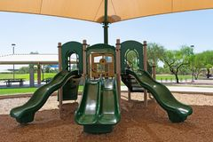 Corrediças sob o dossel no campo de jogos em um parque imagens de stock royalty free