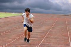 Corredor asiático joven que corre en pista con el fondo de la tormenta del tiempo Fotos de archivo