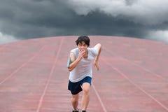 Corredor asiático joven que corre en pista con la tormenta del tiempo en fondo oscuro de cielo nublado Imágenes de archivo libres de regalías