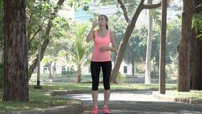 Corredor atlético activo de la mujer joven que activa en parque Entrenamiento femenino apto de la aptitud del deporte Agua potabl almacen de metraje de vídeo