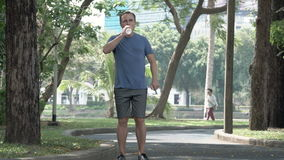Corredor atlético activo del hombre joven que activa en parque Entrenamiento masculino apto de la aptitud del deporte Agua potabl metrajes