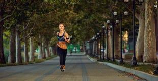 Corredor atlético joven de la muchacha que activa en parque en otoño del verano Imagen de archivo libre de regalías