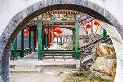 Corredor atrás de uma porta da lua em um jardim tradicional histórico durante o ano novo chinês imagem de stock