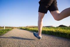 Corredor através dos campos exterior no conceito da luz do sol do verão para o exercício, a aptidão e o estilo de vida saudável foto de stock