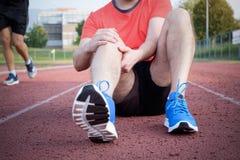 Corredor com o joelho ferido na trilha imagens de stock