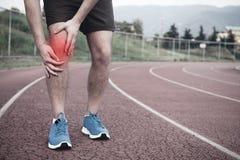 Corredor con lesión del deporte fotos de archivo