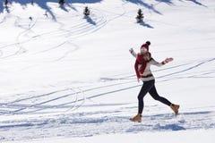 Corredor corriente de la mujer en montañas del invierno en nieve imagen de archivo libre de regalías