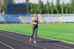Corredor da jovem mulher no estádio da pista Treinamento no tempo de manhã Os povos ostentam e o conceito da aptidão fotografia de stock royalty free