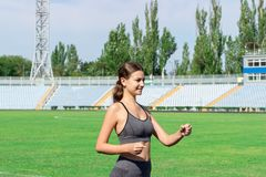 Corredor da jovem mulher no estádio da pista Treinamento no tempo de manhã Os povos ostentam e o conceito da aptidão fotos de stock royalty free