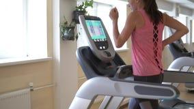 Corredor da jovem mulher no simulador da escada rolante no gym video estoque