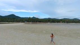 Corredor da menina da raça misturada que movimenta-se em Sandy Beach bonito Koh Phangan, Tailândia Slowmotion aéreo de HD vídeos de arquivo
