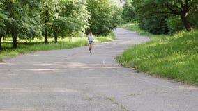 Corredor da moça que corre ao longo da trilha entre o parque em um dia de verão ensolarado video estoque