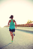 Corredor da mulher da aptidão que corre na estrada Imagens de Stock