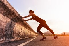 Corredor da mulher do esporte que estica o músculo antes da corrida no longo caminho fotografia de stock