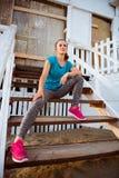Corredor da mulher que senta-se em etapas de madeira de uma cabana da praia Foto de Stock Royalty Free