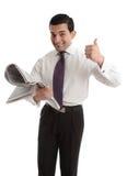 Corredor de bolsa del hombre de negocios con los pulgares del periódico para arriba foto de archivo