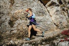Corredor de la mujer con los bastones nórdicos que corren el rastro en el fondo de rocas Fotos de archivo libres de regalías
