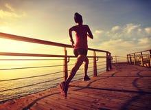 Corredor de la mujer de la aptitud que corre en el paseo marítimo de la playa Fotografía de archivo