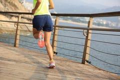 Corredor de la mujer de la aptitud que corre en el paseo marítimo de la playa Imagen de archivo libre de regalías