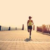 Corredor de la mujer de la aptitud que corre en la playa Imagen de archivo