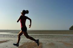 Corredor de la mujer de la aptitud que corre en la playa de la salida del sol Imagenes de archivo