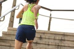 Corredor de la mujer de la aptitud que corre en las escaleras de la piedra de la playa Foto de archivo libre de regalías