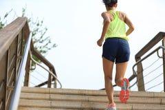 Corredor de la mujer de la aptitud que corre en las escaleras de la piedra de la playa Imágenes de archivo libres de regalías