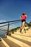Corredor de la mujer de la aptitud que corre en las escaleras de la piedra de la playa Imagen de archivo libre de regalías