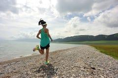 Corredor de la mujer joven de la forma de vida que corre en rastro de la playa de la salida del sol Fotos de archivo