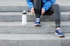 Corredor de la mujer que ata cordones antes de entrenar Maratón Fotografía de archivo