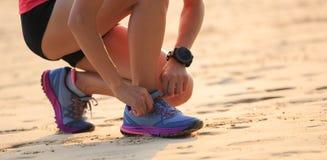 corredor de la mujer que ata el cordón en la playa soleada Foto de archivo libre de regalías